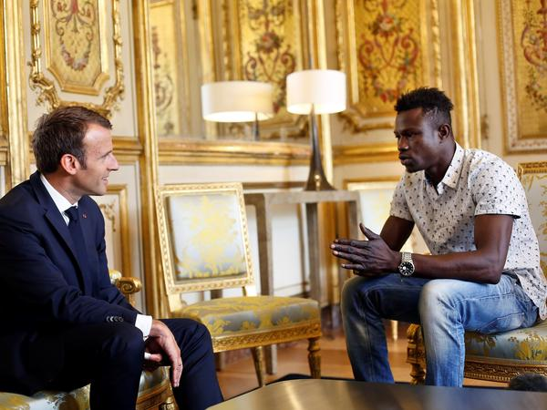 """French President Emmanuel Macron speaks with Mamoudou Gassama at the presidential palace in Paris, on Monday. Macron offered Gassama citizenship for his """"heroic act"""" in saving a four-year-old."""