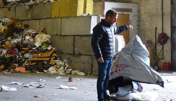 <p>Rogue Waste System's Scott Fowler pulls non-recyclable trash out of the co-mingled recycling mix.</p>