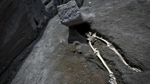 The legs of a skeleton emerge from the ground beneath a large rock, believed to have crushed the victim during the eruption of Mount Vesuvius in A.D. 79. The skeleton was found at Pompeii's archaeological site, near Naples, Italy, and was announced on Tuesday.