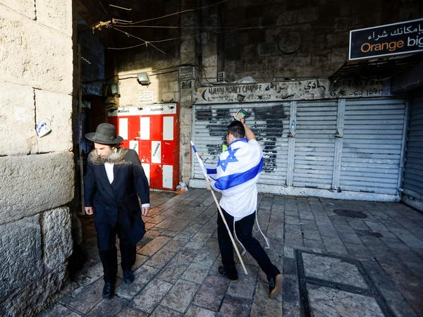 An Israeli draped in the national flag walks past an ultra-Orthodox Jewish man in Jerusalem's Old City on May 13, as Israelis marked Jerusalem Day.