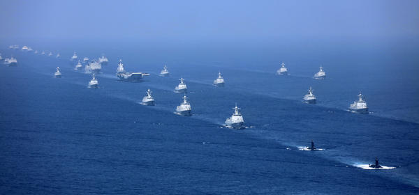 In a photo released by Xinhua News Agency, China's Liaoning aircraft carrier is accompanied by navy frigates and submarines conducting an exercises in the South China Sea, in April.