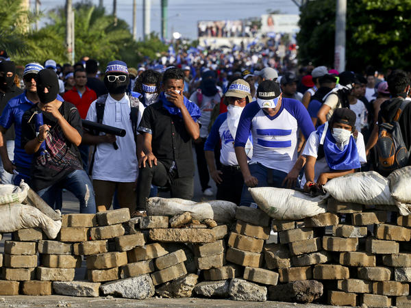 Demonstrators take cover behind a barricade during their march Wednesday in Managua against Nicaraguan President Daniel Ortega.