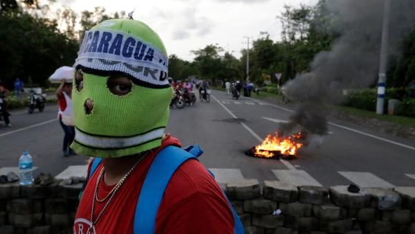 A demonstrator stares down the camera after setting up a barricade in Leon last week.
