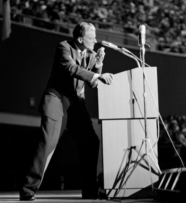 Graham led a movement toward embracing evangelicalism, focused on grace in contrast to fundamentalists, who spoke of damnation. He speaks here before the combined Texas Baptist World Mission and State Evangelistic Conference in Dallas on Jan. 11, 1959.