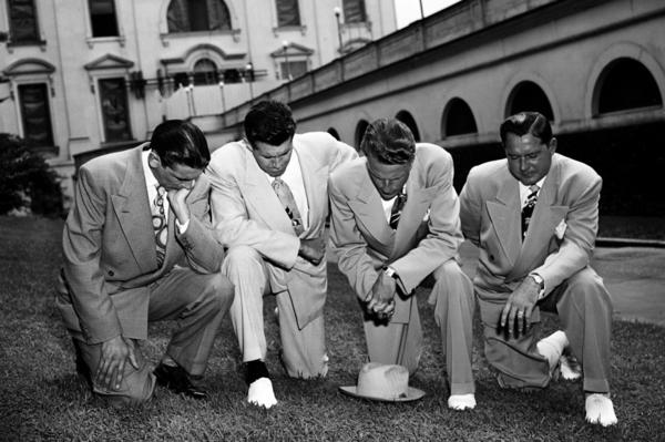 Though Graham always declared himself to be politically neutral, he hovered around the edges of the nation's politics, praying here on the White House lawn on July 14, 1950, asking divine aid for then-President Harry S. Truman in his handling of the Korean crisis. From left are Jerry Beavan, Graham, Clifford Barrows and Grady Wilson.