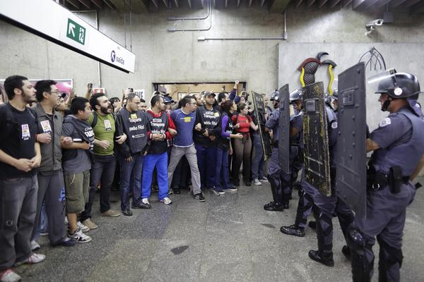 Subway train operators, along with some activists, link arms to block the entrance as they face off with police at the Ana Rosa metro station in Sao Paulo on Friday. The strike is the latest disruption in Brazil that threatens to complicate preparations for the World Cup, which opens next week.
