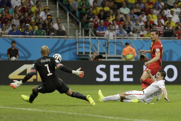 United States' Matt Besler tries to defend as Belgium's Daniel Van Buyten takes a shot on goalkeeper Tim Howard.