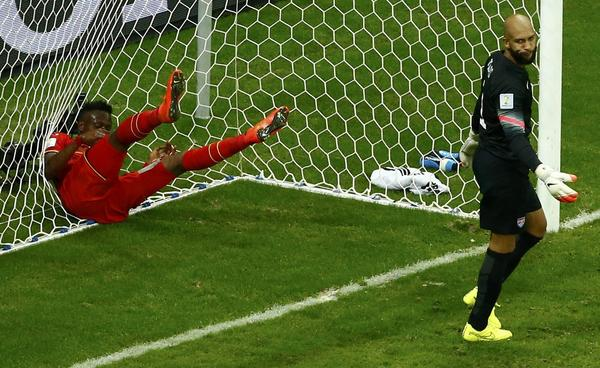 <strong>No Score:</strong> Belgium's Divock Origi throws himself into the net behind goalkeeper Tim Howard of the U.S. during Tuesday's World Cup Round of 16 game.
