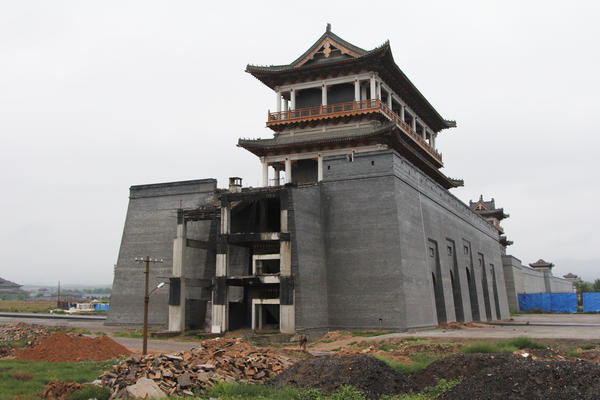 "Luliang's planned ""Liquor City"" has run short of funding. Workers have yet to finish this replica of the Great Wall, which is supposed to surround a massive factory complex producing <em>baijiu</em>, an often expensive Chinese hard liquor."