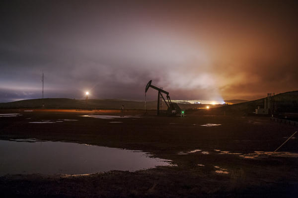 Flares and electric lights on oil well pads illuminate low-hanging clouds near Watford City, North Dakota.