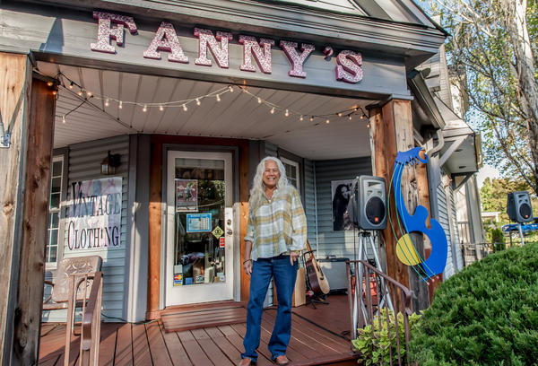 June Millington, the author of the memoir <em>Land of a Thousand Bridges: Island Girl in a Rock & Roll World</em>, on the porch of the Fanny's House of Music in East Nashville. The shop is named after Millington's band, Fanny.