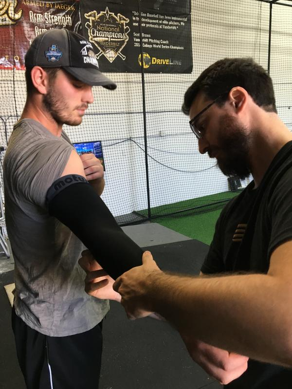 Driveline Baseball research assistant Michael O'Connell puts a sleeve on pitcher Luke Glavin's throwing arm. The sleeve, a wearable designed by Motus, measures factors such as elbow stress and arm speed.