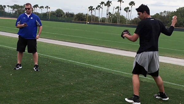 Ben Hansen (left) watches data on a hand-held device as Pittsburgh Pirates prospect Matt Benedict throws a ball. Benedict is wearing sensors that recorded 39 sets of measurements.