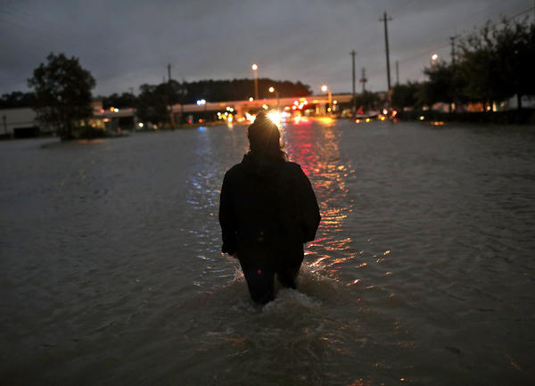 A Houston resident walks through waist-deep water while evacuating her home after severe flooding following Hurricane Harvey in north Houston.