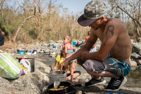 Luis Fernandez, 27, fries plantains over firewood on the banks of the Calabaza River.