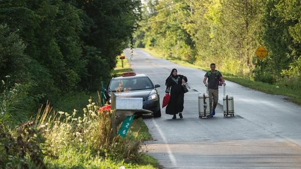A cab drops off a couple of asylum seekers at the U.S.-Canada border near Champlain, N.Y., on Aug. 20.