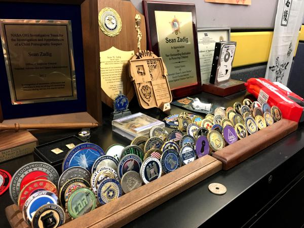 As a former federal agent, Zadig has a collection of these so-called challenge coins, which are exchanged by law enforcement agents during visits.
