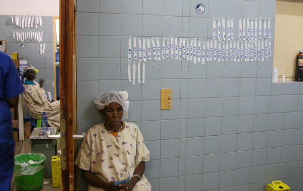 A patient awaiting cataract surgery at the Bisidimo Hospital sits by a wall with strips of tape. After surgery, the tape, with the initials of the doctor, is used to hold the patient's bandages in place. The number on the tape serves as a running tally of that doctor's surgeries for the day.