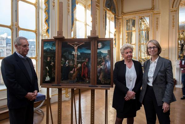 Standingwith French Culture Minister Françoise Nyssen, Christopher Bromberg and Henrietta Schubert, grandchildren of Henry and Hertha Bromberg, view Flemish painter Joachim Patinir's <em>Triptych of the Crucifixion</em>, which was returned to them Monday by the French state.