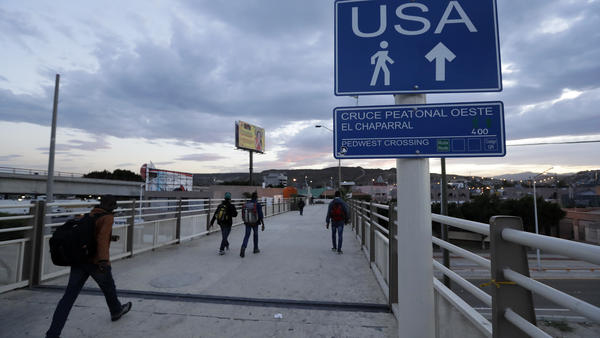 Immigrants make their way towards the border crossing in Tijuana, Mexico.