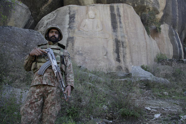 A Pakistani soldier stands in front of a 7th century rock-face carving of a Buddha above the village of Jahanabad in the Swat Valley. It was restored by Italian archaeologists in 2016, after the Taliban partially destroyed it with explosives.