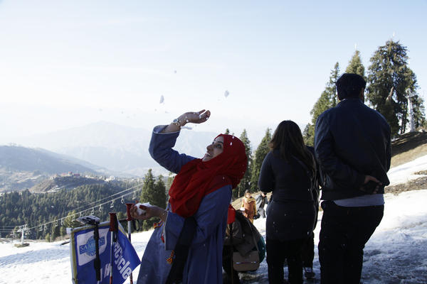 At a Swat Valley ski resort, a woman dodges snowballs. Domestic tourism is strong to the Swat Valley, although residents have struggled to revive their international tourism market.