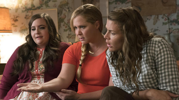 Aidy Bryant (left) and Busy Phillips play best friends to  Schumer's Renee in the almost-reverse-makeover movie.