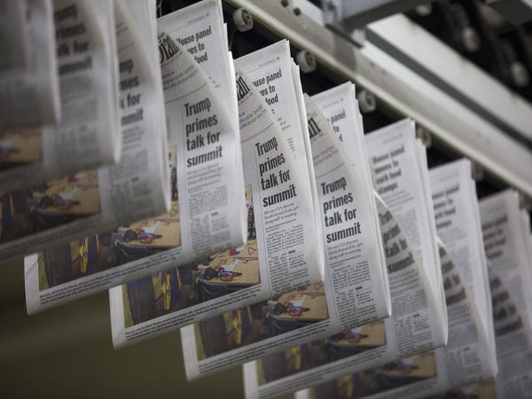 A daily edition of <em>The Columbian</em> passes overhead at the paper's printing press in Vancouver, Wash.