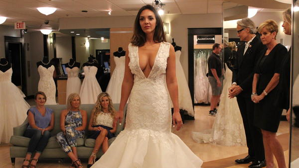 Bride Lindsey Morgan tries on a popular style on an episode of TLC's <em>Say Yes to the Dress Atlanta. </em>Host Monte Durham stands second from right.