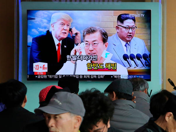 "People watch a TV showing images of North Korean leader Kim Jong Un (right), South Korean President Moon Jae-in and U.S. President Donald Trump — and the words ""Thawing Korean Peninsula"" — at a railway station in Seoul, South Korea on March 7."