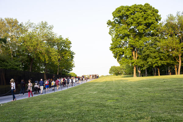 Visitors walk along the Vietnam Veterans Memorial. A new sign warns visitors that human remains left there will not be added to the memorial's permanent collection.