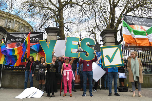 """Yes"" vote campaigners cover abortion-rights opponents' posters with Irish and rainbow flags outside the Irish parliament in Dublin on May 4."