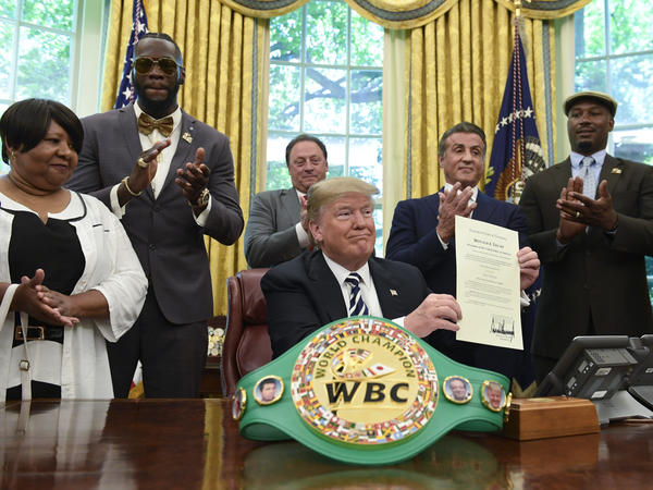 President Donald Trump, center, pardons Jack Johnson, boxing's first black heavyweight champion, during an event in the Oval Office of the White House on May 24. Trump is joined by, from left: Linda Haywood; Deontay Wilder; Keith Frankel; Sylvester Stallone; Lennox Lewis; Mauricio Sulaiman Saldivar.