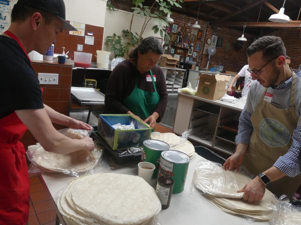 """As part of the prep, Wayne Cheung (left), Wendy Dwyer and Michael Kyle separate tortillas. """"I find it very gratifying,"""" says Cheung, who started volunteering in February. """"I might do this as long as the project lasts."""""""