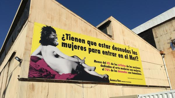 """Beyond the Streets"" boasts one of the Guerrilla Girls' most well-known billboards — in Spanish. It translates to ""Do women have to be naked to get into the Met? Less than 4 percent of the artists in the modern art sections are women, but 76 percent of the nudes are female."""