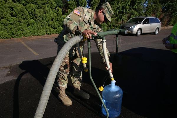 <p>A National Guard soldier fills a container of water in the parking lot of a bowling alley in Salem.</p>