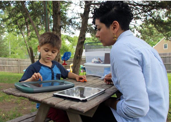 Five-year-old Ridley Fitzmorris works with therapist Ashley Estrada in his backyard. In Kansas, some children with autism end up on long waitlists for therapy.