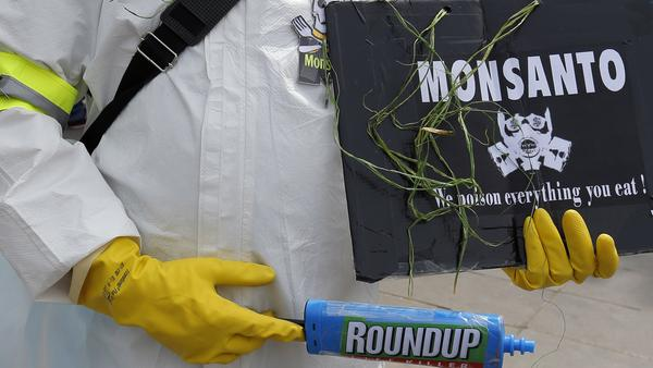 A protester takes part in a March Against Monsanto in Paris in May 2016. The European chemical and pharmaceutical giant Bayer is buying Monsanto — and dropping the U.S. company's now-controversial name.