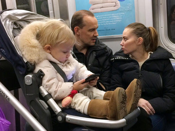 A child plays with a mobile phone while riding in a New York subway in December. Two major Apple investors urged the iPhone maker to take action to curb growing smartphone use among children.
