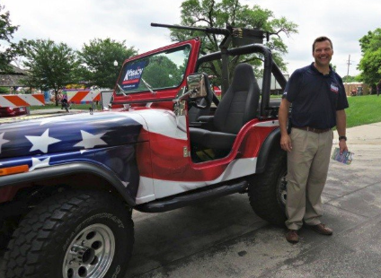 """Kris Kobach rode what he calls a """"patriotic jeep"""" through the Old Shawnee Days parade with a machine gun replica mounted on top."""