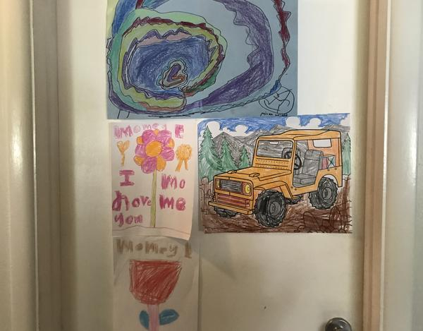 """Colorful illustrations and """"I love you Mommy"""" notes cover foster parents Elizabeth and Kate Dumbaugh's bedroom door."""