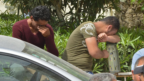 People wait for news of friends and relatives in the Tunisian town of Sfax on Monday after the deadly sinking of a migrant boat off the Tunisian coast over the weekend.