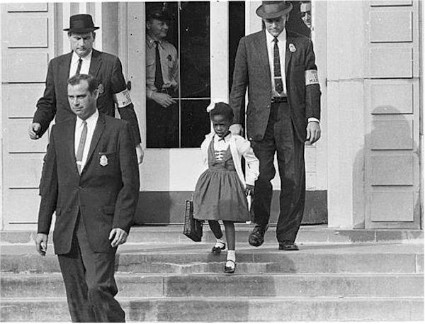 Ruby Bridges is escorted to school.