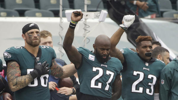 Philadelphia Eagles' Chris Long (56), Malcolm Jenkins (27) and Rodney McLeod (23) gesture during the national anthem before an NFL game against the Arizona Cardinals on Oct. 8, 2017, in Philadelphia.