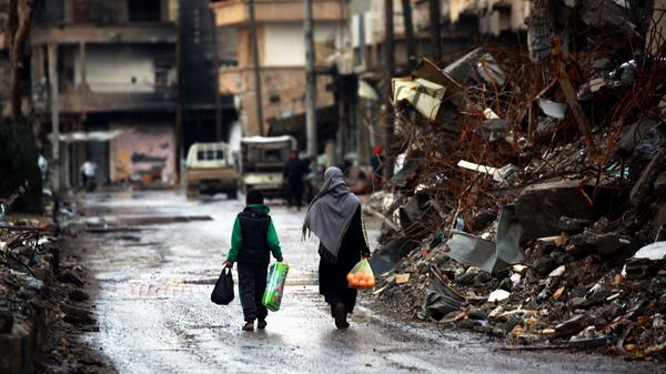 Syrians walk along a destroyed street in Raqqa in February.