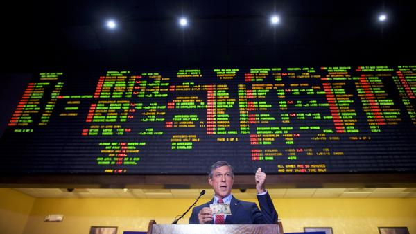 Delaware Gov. John Carney holds a $10 bill he used to place the first bet at Dover Downs Casino on Tuesday in Dover, Del. Delaware is the first state to launch legal sports betting since a Supreme Court decision allowed states to legalize such gambling.