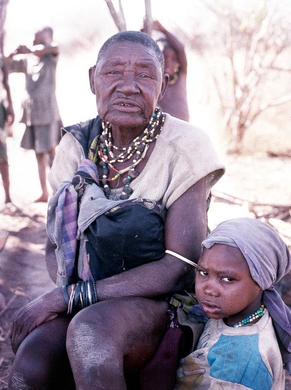 A Tanzanian Hadza grandmother sits in the shade with her grandchild during the 1995 dry season.