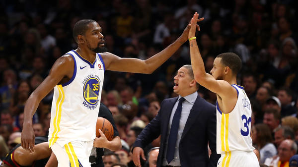 Kevin Durant and Stephen Curry of the Golden State Warriors celebrate as coach Tyronn Lue of the Cleveland Cavaliers looks on Friday during Game Four of the 2018 NBA Finals in Cleveland. It's the team's third NBA title in four years.