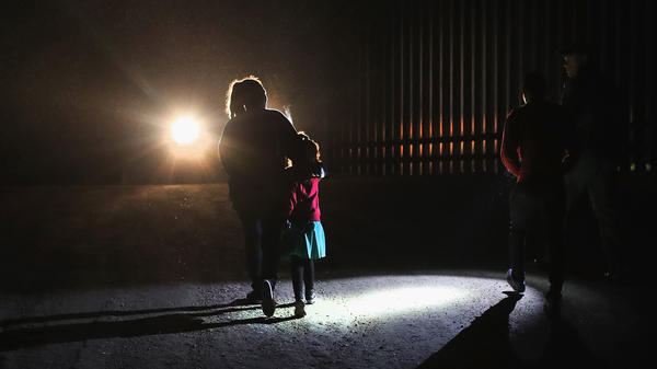 A Honduran mother walks with her children next to the U.S.-Mexico border fence as they turned themselves in to Border Patrol agents in February near Penitas, Texas.