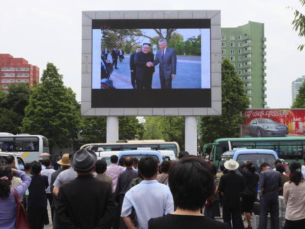 People in Pyongyang watch a large screen at the main train station airing video of North Korean leader Kim Jong Un being greeted by Singapore Prime Minister Lee Hsien Loong on Monday.